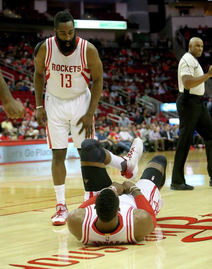 James Harden comes to the assistance of Dwight Howard, who injured his ankle early in the first quarter and did not return. Photo: Gary Coronado, Staff / © 2015 Houston Chronicle