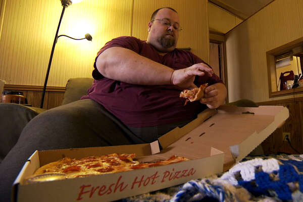 "Chad Dean eating pizza in his Bryan living room prior to weight-loss surgery. His story aired on TLC's ""My 600-lb Life"" on Jan. 20, 2016."