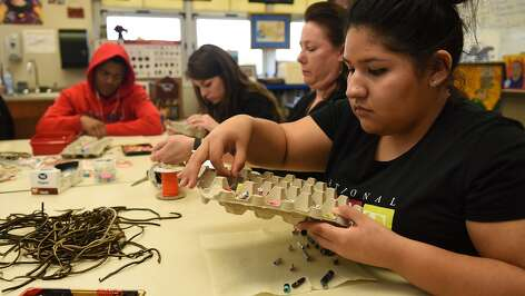 Hauke Alternative High School sophomore Dulce Reyna, 16, right, puts together kits of paper beads for making beaded jewelry which will be donated to Pro-ject Row House in Third Ward to raise funds for local artists during class on Jan. 13, 2016. (Photo by Jerry Baker/Freelance)