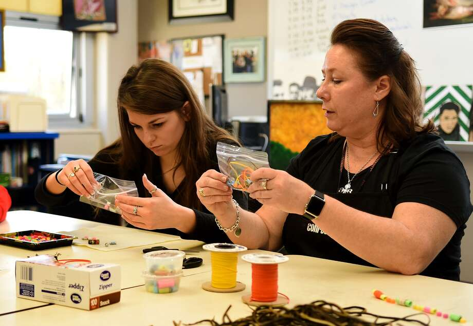 Hauke Alternative High School junior Loni Sutton, left, and art teacher Terri Sanders put together kits of paper beads for making beaded jewelry which will be donated to Project Row Houses in Houston's Third Ward to raise funds for local artists. Photo: Jerry Baker, Freelance