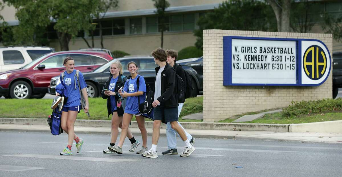 FILE - Students from Alamo Heights High School walk across Broadway after the final bell rang on Thursday, Jan. 14, 2015. The school is adding an armed police officer for the remainder of the school year following the massacre of 17 people, including students and teachers, at a Florida high school.