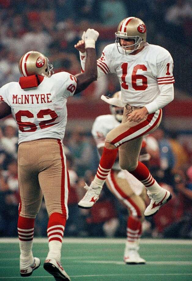 San Francisco 49ers quarterback Joe Montana (16) celebrates with lineman Guy McIntyre after a third quarter touchdown against the Denver Broncos in Super Bowl XIV, Jan. 28, 1990, in New Orleans. Photo: Mark Duncan, AP