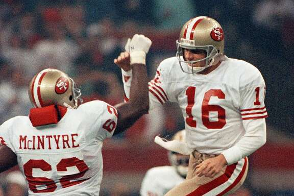San Francisco 49ers quarterback Joe Montana (16) celebrates with lineman Guy McIntyre after a third quarter touchdown against the Denver Broncos in Super Bowl XIV, Jan. 28, 1990, in New Orleans. Montana was named Super Bowl MVP for the third time after completing 22 of 29 passes for 297 yards and five touchdowns as the 49ers won 55-10, the most lopsided Super Bowl to date. The Broncos had lost three Super Bowls in four years. (AP Photo/Mark Duncan)