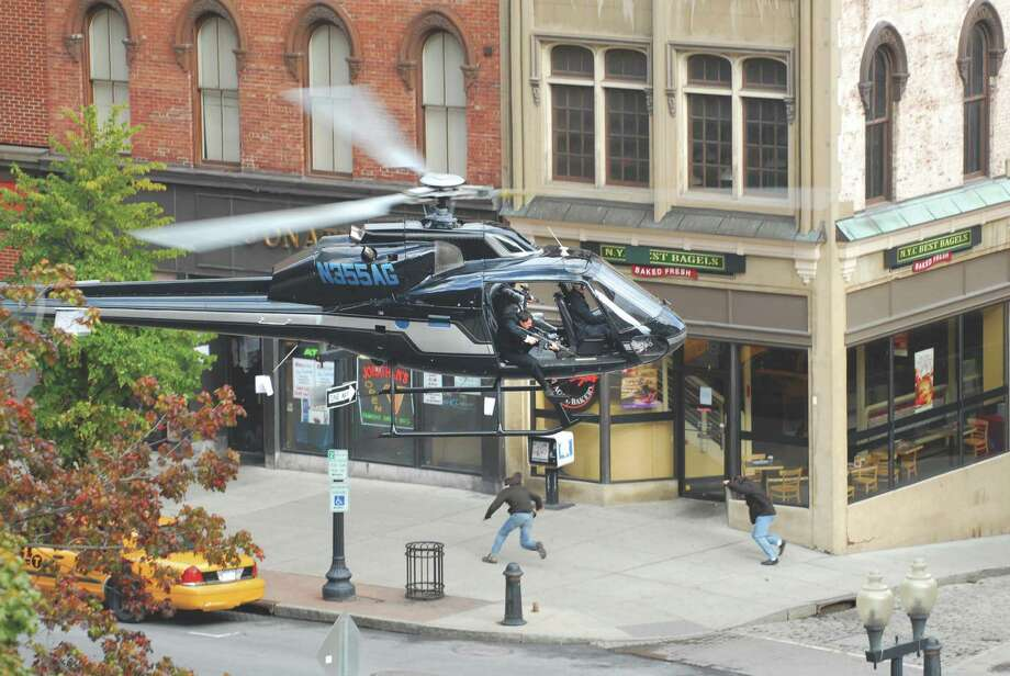 "Actors in a low hovering helicopter pretend to fire weapons during a car chase during filming for the movie ""The Other Guys"" on Pearl St. in Albany, NY on Sunday, Oct. 4, 2009.   (Paul Buckowski / Times Union) Photo: PAUL BUCKOWSKI / 00005776A"