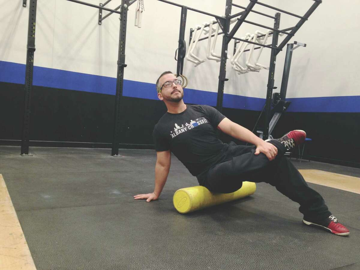 James McDermott demonstrates the hip release movement on a foam roller at Albany Crossfit in Colonie. (Carin Lane / Times Union)