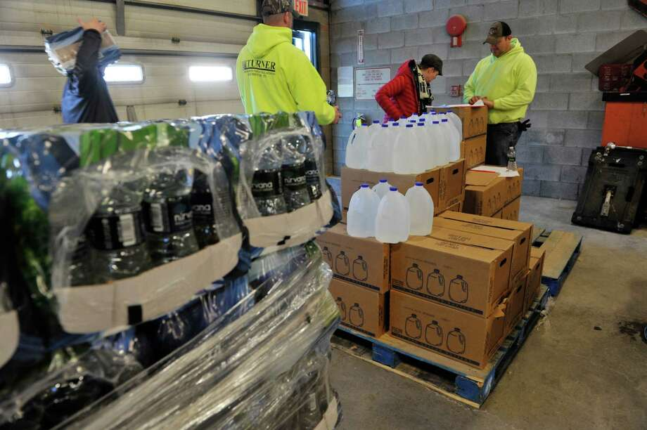Employees with the Halfmoon Highway Department hand out water to residents on Thursday, Jan. 21, 2016, in Clifton Park, N.Y.  (Paul Buckowski / Times Union) Photo: PAUL BUCKOWSKI / 10035095A
