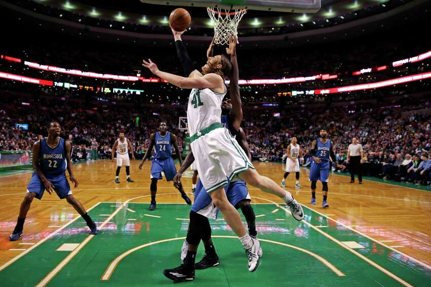 Boston Celtics center Kelly Olynyk (41) shoots a reverse lay-up on a drive to the basket against the Minnesota Timberwolves during the first quarter of an NBA basketball game in Boston, Friday, Dec. 19, 2014. (AP Photo/Charles Krupa)