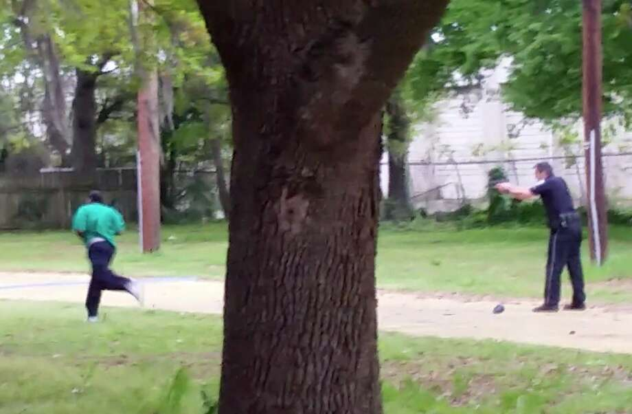 In this April 4, 2015, frame from video provided by Attorney L. Chris Stewart representing the family of Walter Lamer Scott, Scott runs away from city patrolman Michael Thomas Slager, right, in North Charleston, S.C. Slager was charged with murder on Tuesday, April 7, hours after law enforcement officials viewed the dramatic video that appears to show him shooting a fleeing Scott several times in the back. (AP Photo/Courtesy of L. Chris Stewart) Photo: Uncredited, Associated Press