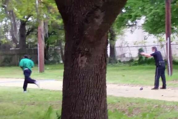 In this April 4, 2015, frame from video provided by Attorney L. Chris Stewart representing the family of Walter Lamer Scott, Scott runs away from city patrolman Michael Thomas Slager, right, in North Charleston, S.C. Slager was charged with murder on Tuesday, April 7, hours after law enforcement officials viewed the dramatic video that appears to show him shooting a fleeing Scott several times in the back. (AP Photo/Courtesy of L. Chris Stewart)