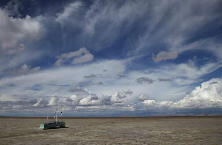 In this Jan. 12, 2016 photo, an abandoned boat lies on the dried up lake bed of Lake Poopo, on the outskirts of Untavi, Bolivia. Drought caused by the recurrent El Nino meteorological phenomenon is considered the main driver of the lake's demise. Along with glacial melting, authorities say another factor is the diversion of water from Poopo's tributaries, mostly for mining but also for agriculture. (AP Photo/Juan Karita)