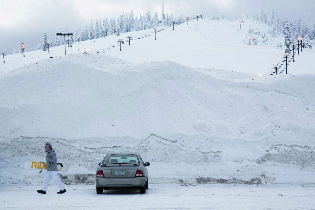 A snowboarder leaves his car with his snowboard for night skiing at the Summit at Snoqualmie on Wednesday, Jan. 13, 2016.