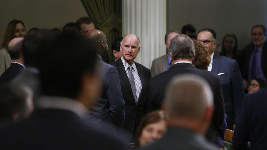 Lawmakers greet Gov. Jerry Brown as he arrives on the Assembly floor to deliver his annual State of the State address. Photo: Paul Chinn, The Chronicle