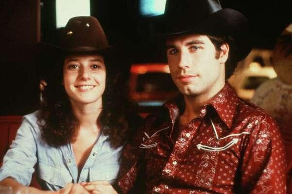 "CIRCA 1980: Actor John Travolta and Debra Winger pose in a scene during the Paramount Pictures movie 'Urban Cowboy"" circa 1980."