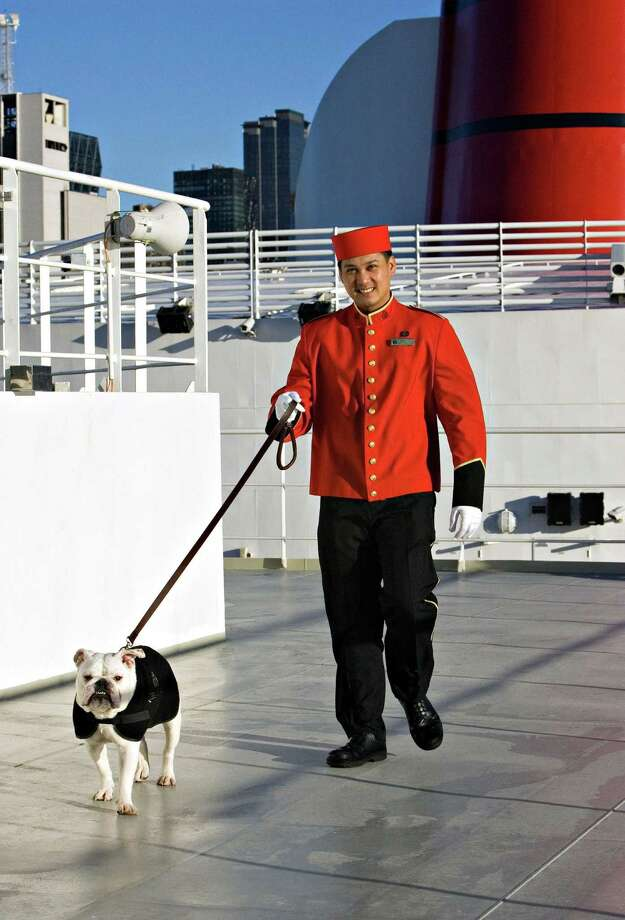 This undated photo from Cunard shows the cruise line's kennel master walking a dog on the top deck of the Queen Mary 2. The ship is going into drydock later this year for a renovation that will add family staterooms and rooms for solo travelers, as well as adding kennel space for canine passengers. (Cunard via AP) ORG XMIT: MER2016011410463460 / Cunard