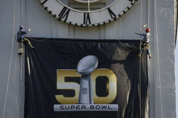 Steeplejack Jim Phelan (right) of JC Phelan & Son and his nephew Tyrone Mancuso work on the Ferry Building as they hang a banner for the upcoming Super Bowl 50 on Thursday, January 21, 2016 in San Francisco, Calif.
