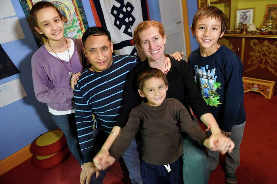 Tashi and Jessica Palden, seated, are surrounded by their children Maura, 13, left, Tinley, 9, right, and Rinchen, 5, on Tuesday, Dec. 8, 2015, at Little Moon Tibetan Gift Shop in Albany, N.Y. The family is preparing to live in India for one year. (Cindy Schultz / Times Union) Photo: Cindy Schultz / 10034560A