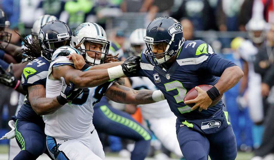 Seattle Seahawks quarterback Russell Wilson, right, tries to fend off Carolina Panthers outside linebacker Shaq Thompson, left, in the second half of an NFL football game, Sunday, Oct. 18, 2015, in Seattle. Photo: Elaine Thompson, Associated Press / AP