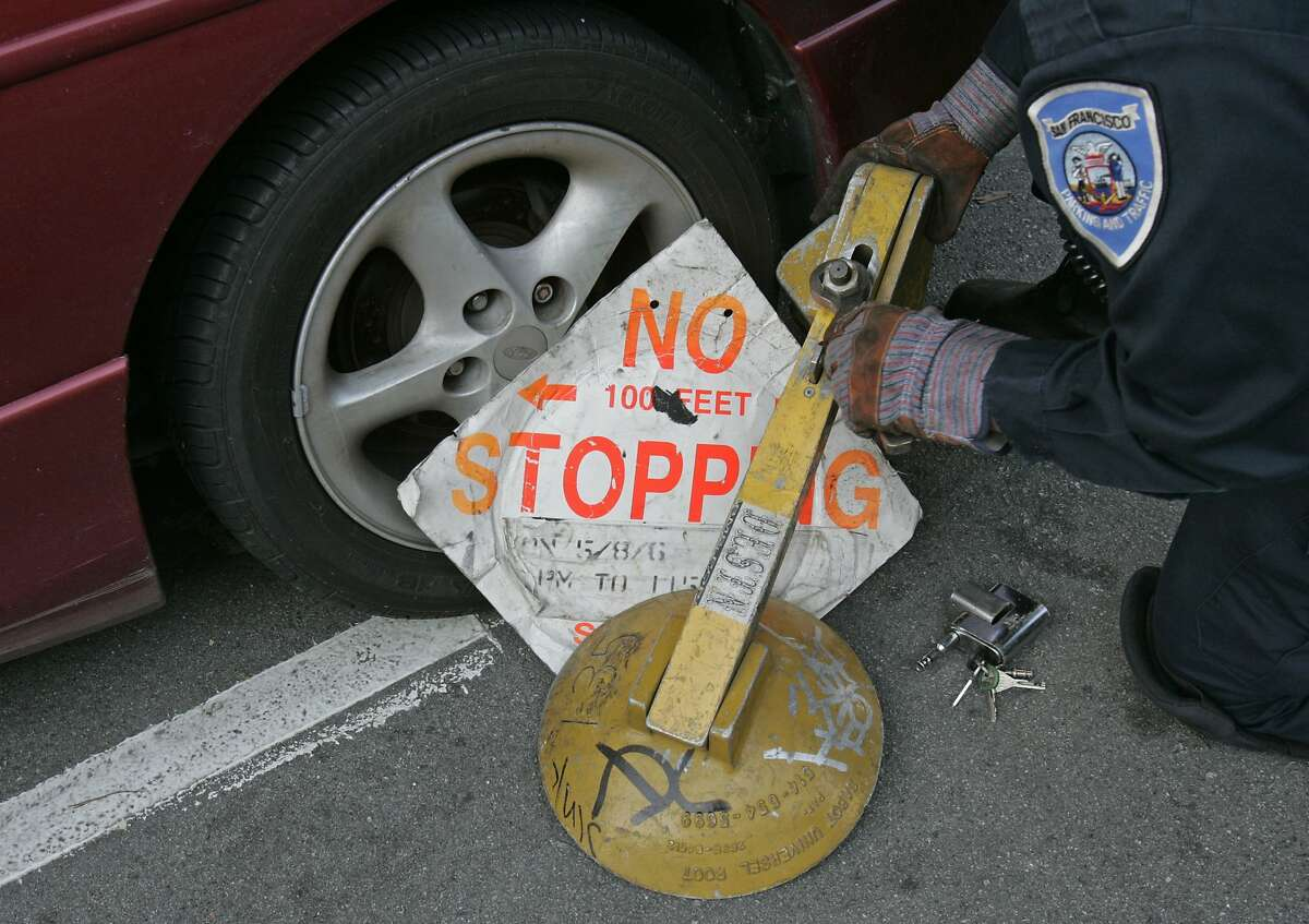 scofflaws_0074_df.jpg Bill Self removes a boot from a wheel of a car on Haight Street. The car is being towed away to an impound lot since the owner did not come forward to pay $745. for 9 tickets after three days of the boot. Bill Self, Parking Control Officer, and his partner are using new technology to catch people who are not paying their parking tickets. In a van equipped with cameras which photograph license plates they are able to obtain information about outstanding parking tickets. Photographed in San Francisco on 12/20/06. (Deanne Fitzmaurice/ The Chronicle)