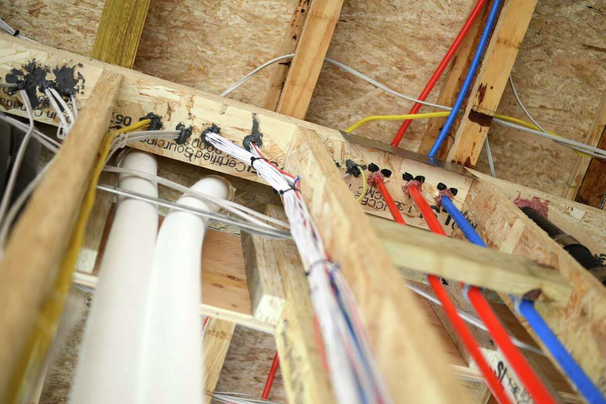 Pictured are several behind the walls elements that make the Greenwich house energy efficient and smart. The blue and red Pex Tubing is used to deliver hot and cold water throughout the house,and has largely replaced copper pipes within homes. On the left are the air exchange hoses that pipe fresh outdoor air into the home, and onthe stud are smart tech wires that will help operate lights, heating and air conditioning, security, fire, and other safety tech throughout the home.