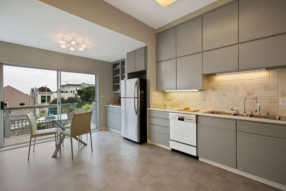 Task lights illuminate the counters beneath handleless cabinetry in the eat-in kitchen. Photo: Open Homes Photography