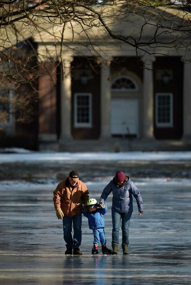 Three-year-old Graham Singer, center, gets his first ice skating lesson from grandfather Steve Mitchell, left, and mom, Suzanne Singer Thursday afternoon, Jan. 21, 2016, at the man made ice skating rink at the Saratoga State Park in Saratoga Springs, N.Y. (Skip Dickstein/Times Union) Photo: SKIP DICKSTEIN