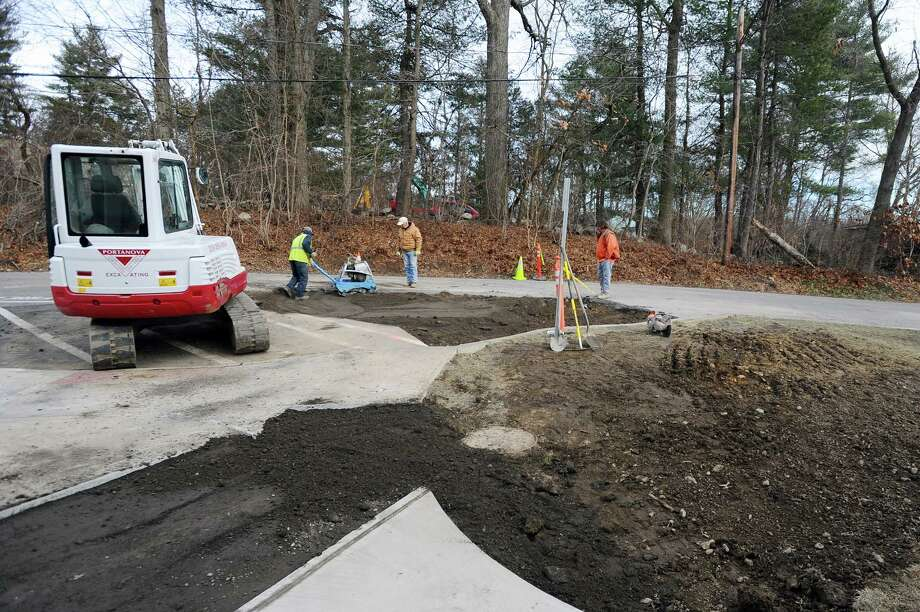 Workers finish repairing a sinkhole that formed in the driveway behind Turn of River Middle School after a water main broke before school opened Tuesday morning. Photo: Michael Cummo / Hearst Connecticut Media / Stamford Advocate