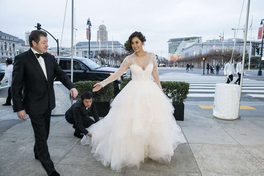 Nune Worraruji is assisted with her gown after arriving at City Hall with James Tyree (left) to attend the San Francisco Ballet 2016 Opening Night Gala at San Francisco City Hall in San Francisco, Calif., on Thursday, January 21, 2016. Photo: Laura Morton, Special To The Chronicle
