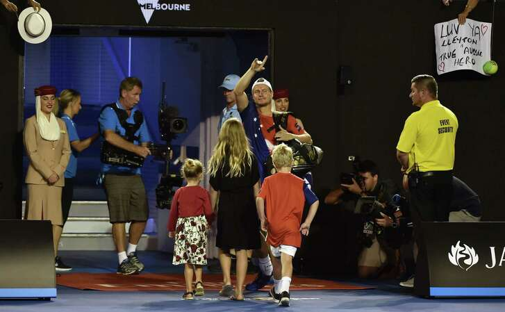 With his children in tow, countryman Lleyton Hewitt bids the crowd a final farewell as he exits the court after losing to David Ferrer in his final match as a professional at the Australian Open in Melbourne on Thursday.