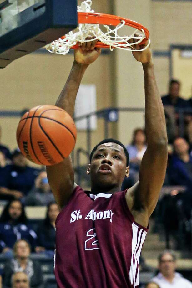 Charles Bassey spends some time in the net stuffing the ball for the Yellow Jackets as Central Catholic plays St. Anthony in boys basketball at Greehey Arena on Jan. 21, 2016. Photo: Tom Reel /San Antonio Express-News / 2016 SAN ANTONIO EXPRESS-NEWS