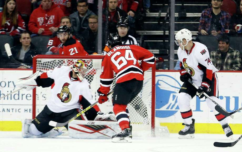 New Jersey Devils center Joseph Blandisi (64) scores his first career goal against Ottawa Senators goalie Craig Anderson (41) during the first period of an NHL hockey game, Thursday, Jan. 21, 2016, in Newark, N.J. (AP Photo/Julio Cortez) ORG XMIT: NJJC104 Photo: Julio Cortez / AP