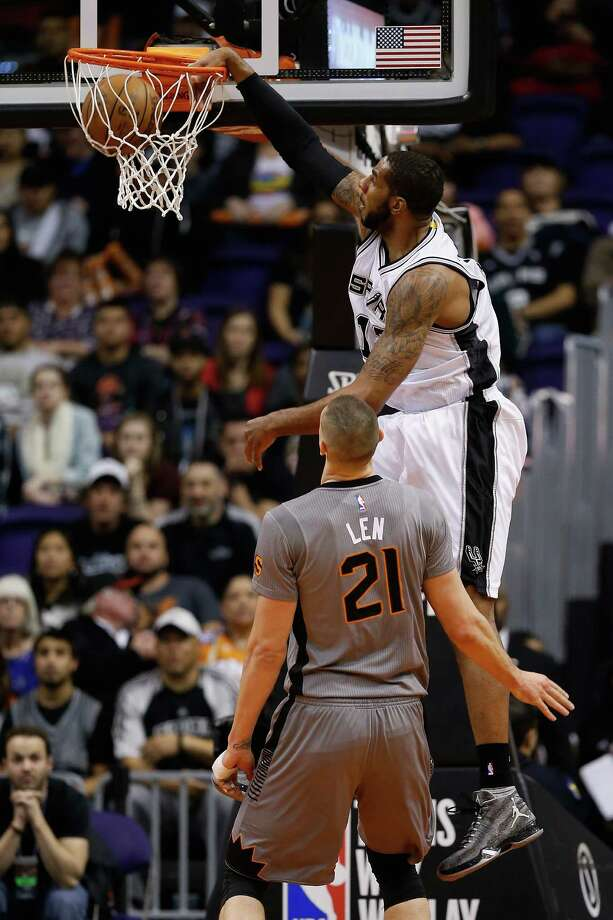 PHOENIX, AZ - JANUARY 21:  LaMarcus Aldridge #12 of the San Antonio Spurs slam dunks against the Phoenix Suns during the first half of the NBA game at Talking Stick Resort Arena on January 21, 2016 in Phoenix, Arizona.  NOTE TO USER: User expressly acknowledges and agrees that, by downloading and or using this photograph, User is consenting to the terms and conditions of the Getty Images License Agreement. Photo: Christian Petersen, Getty Images / 2016 Getty Images