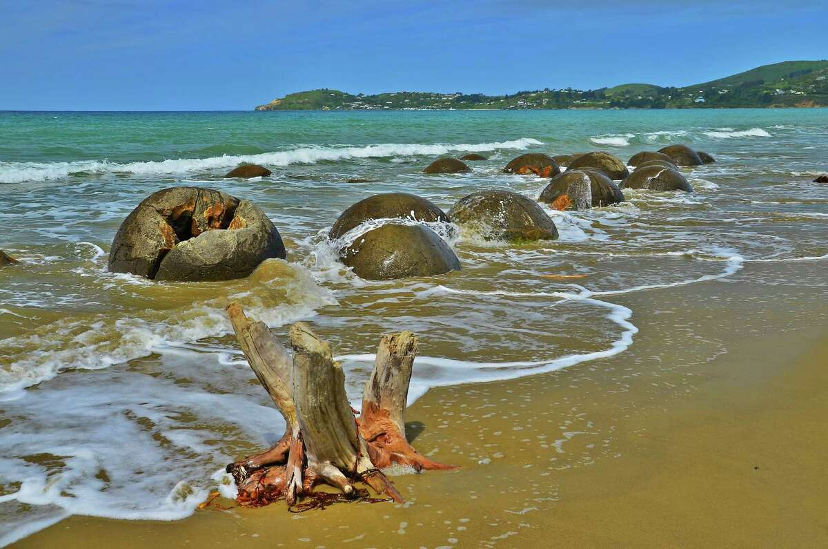 """Moeraki Boulders in Koekohe Beach, New Zealand: Aside from its beautiful surroundings, this beach is mainly known for its """"dragon eggs."""" Some legends say that these boulders are the remains of wreckage from a large sailing canoe."""