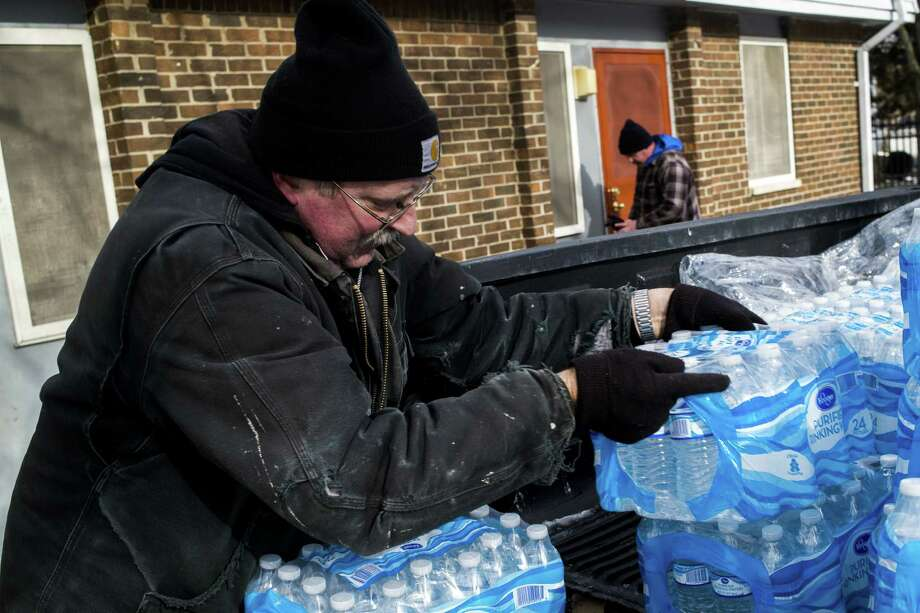 Maintenance technicians Mike Young, front left, and Chris Sprague deliver cases of water to residents on Tuesday, Jan. 19, 2016 at River Park Apartments in Flint, Mich. After weeks without water being distributed, the residents are finally getting bottled water delivered to their doorsteps for the first time by the Flint Hoursing Commision. (Jake May/The Flint Journal-MLive.com via AP) ORG XMIT: MIFLI103 Photo: Jake May | MLive.com / The Flint Journal