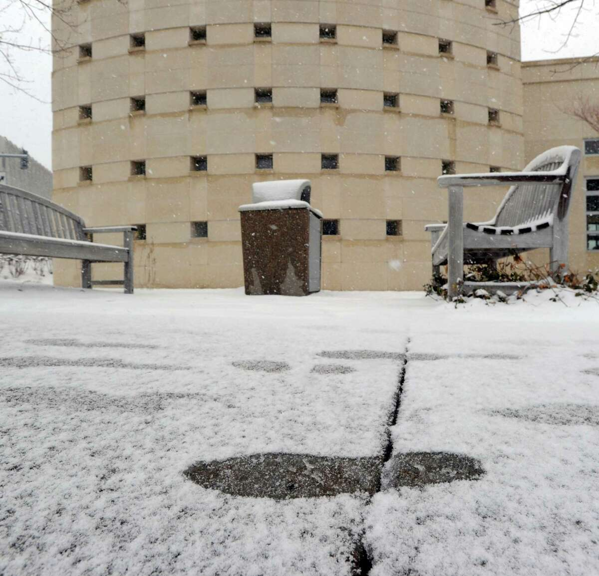 A foot print in the snow on a walkway outside of Greenwich Library during the snow storm that hit the area, Greenwich, Conn., Friday, March 20, 2015. A snow storm could hit Greenwich this Saturday and Sunday.