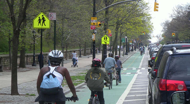 Looking south at Prospect Park West protected bike lane on a cloudy midday.
