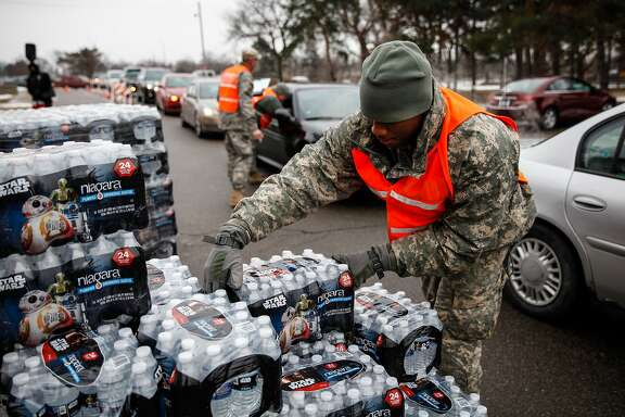FLINT, MI - JANUARY 21:  Army National Guard Specialist David Brown loads bottled water into waiting cars at a fire station on January 21, 2016 in Flint, Michigan. Residents can go daily to fire stations in the city to pick up more water.  (Photo by Sarah Rice/Getty Images)
