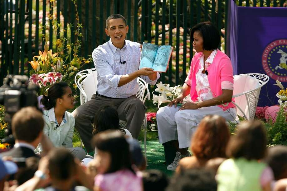 "WASHINGTON - APRIL 05:  U.S. President Barack Obama (C) reads ""Green Eggs and Ham,"" by Dr. Suess, for a group of children and his family, first lady Michelle Obama (R) and daughters Malia Obama (L), 11, and Sasha Obama, 8, during the Easter Egg Roll at the White House April 5, 2010 in Washington, DC.  About 30,000 people are expected to attend attended the 132-year-old tradition of rolling colored eggs down the South Lawn of the White House.  (Photo by Chip Somodevilla/Getty Images) *** Local Caption *** Barack Obama;Michelle Obama;Malia Obama;Sasha Obama Photo: Chip Somodevilla, Getty Images / 2010 Getty Images"