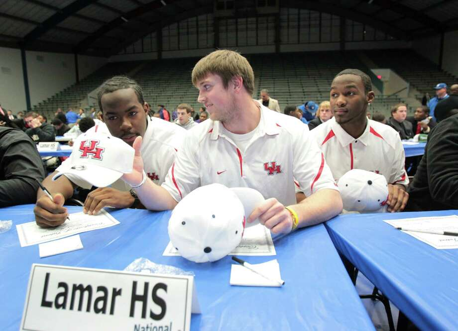 (l-r) After signing their letters of intent to play football at the University of Houston, Lamar High school seniors Kourtland Akins, Bram Kohlhausen and Earl Foster, prepare to put on their University of Houston ball caps. HISD athletes gathered at Delmar Fieldhouse Wednesday February 2, 2011 for  a National Signing Day ceremony. (Billy Smith II / Houston Chronicle) Photo: Billy Smith II, HC Staff / Houston Chronicle