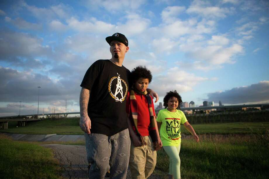 Rapper Paul Wall walks along the White Oak Bayou with his son William Wall, 9, and his daughter Noelle Wall, 8, Thursday, Jan. 7, 2016, in Houston. The family often has long walks as a way to show the importance of outdoor activities to their children. ( Marie D. De Jesus / Marie D. De Jesus ) Photo: Marie D. De Jesus, Staff / © 2016 Marie D. De Jesus