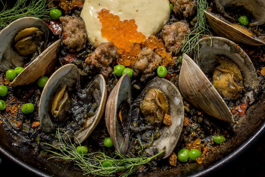 The Arroz Negro paella ($32) at La Marcha in Berkeley features black rice stained with squid ink and topped with clams, sausage, peas and salmon roe. Photo: John Storey