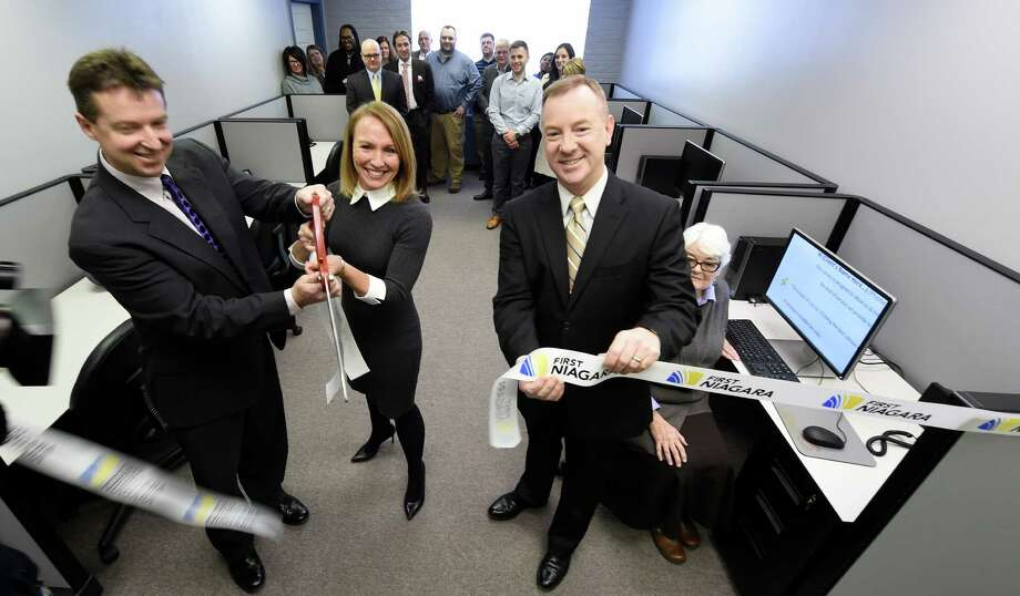 Christopher T. Burke, executive director, right cuts the ribbon on the new First Niagara call center at the Northeastern Association of the Blind's offices Jan. 22, 2016 in Albany, N.Y.  Joining Burke are Michael Collins, chairman of the board of NABA's trustees, left, Kelli Arnold, market executive, First Niagara, second from left and Diane Clancy, NABA volunteer, right.        (Skip Dickstein/Times Union) Photo: SKIP DICKSTEIN / 10035107A