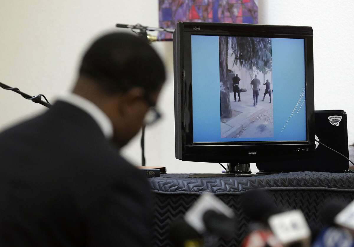 Attorney Adante D. Pointer, left, speaks at a news conference in San Francisco, Monday, Jan. 18, 2016, as a video is displayed of the San Francisco police shooting of Mario Woods who police say appeared to raise a knife and approach one of the officers. The family of Woods has asked the U.S. Department of Justice to investigate the officers who shot Woods on Dec. 2, 2015, and review the San Francisco police department's use of deadly force, stops, and detention and searches of African American and Latinos citizens for possible civil rights violations. (AP Photo/Jeff Chiu)