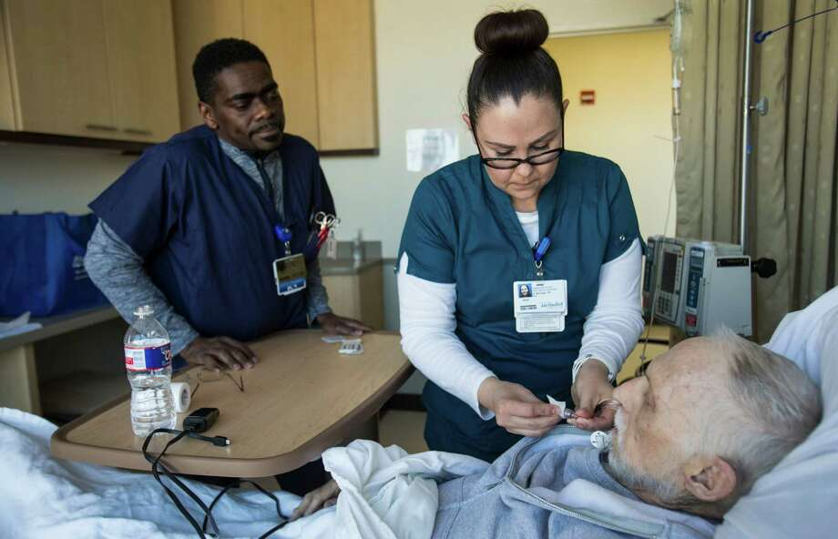 David Raven, left, and Anya Montoya work with patient Neil Harrison at Houston Methodist Cancer Center on Friday. As energy companies expect more layoffs, the health care sector continues to see robust hiring. Photo: Brett Coomer, Staff / © 2016 Houston Chronicle