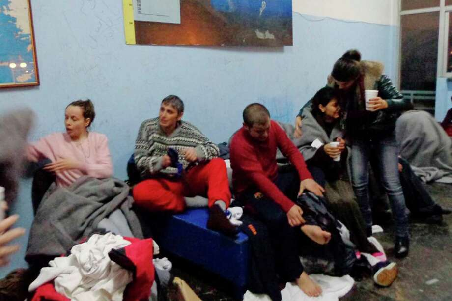 Survivors change clothes at Kalymnos island after a rescue operation by the coast guard Friday, Jan. 22, 2016. A wooden sailboat carrying an undetermined number of people sank off the islet of Kalolimnos near the Greek southeastern island of Kalymnos. A number of people died in two separate incidents of boats smuggling migrants or refugees sinking off two Greek islands overnight into Friday. Dozens survived, and a search and rescue operation was underway for more potential survivors. (Giorgos Drosos/Kalymnos-News.gr via AP) ORG XMIT: XTS101 Photo: Giorgos Drosos / Kalymnos-News.gr