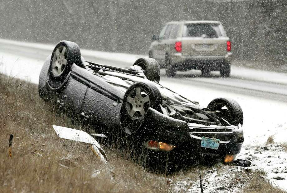 An overturn vehicle rests on the shoulder of a snow-covered U.S. 522 near Gainesboro, Va.,  Friday, Jan. 22, 2016.  There no injuries in the accident. A blizzard menacing the Eastern United States started dumping snow in Virginia, Tennessee and other parts of the South on Friday as millions of people in the storm's path prepared for icy roads, possible power outages and other treacherous conditions. (Scott Mason/The Winchester Star via AP) MANDATORY CREDIT  ORG XMIT: VAWIN105 Photo: SCOTT MASON / The Winchester Star