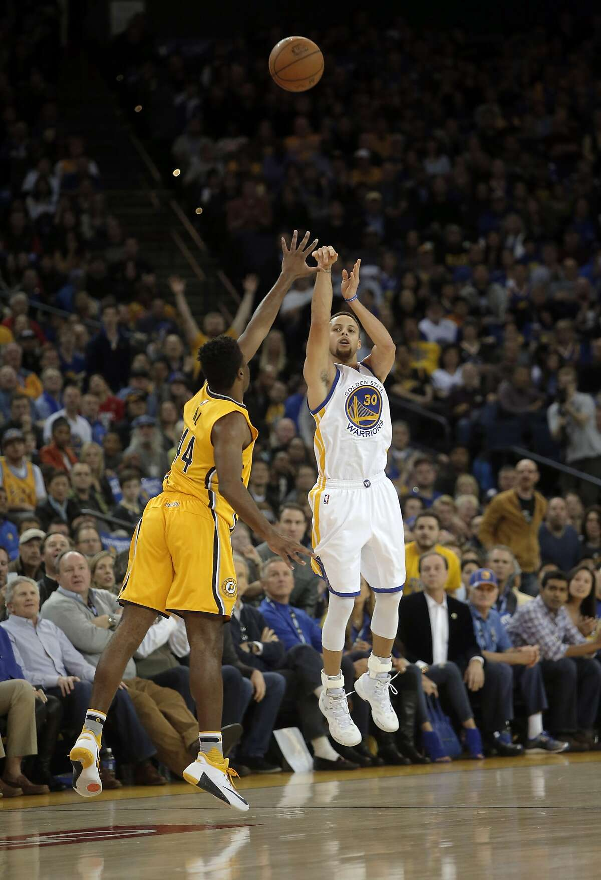 Warriors' Stephen Curry, 30 hits a near half court 3-point-shot to end the first half, as the Golden State Warriors take on the Indiana Pacers in NBA action during the first half at Oracle Arena on Fri. January 22, 2016, in Oakland, Calif.