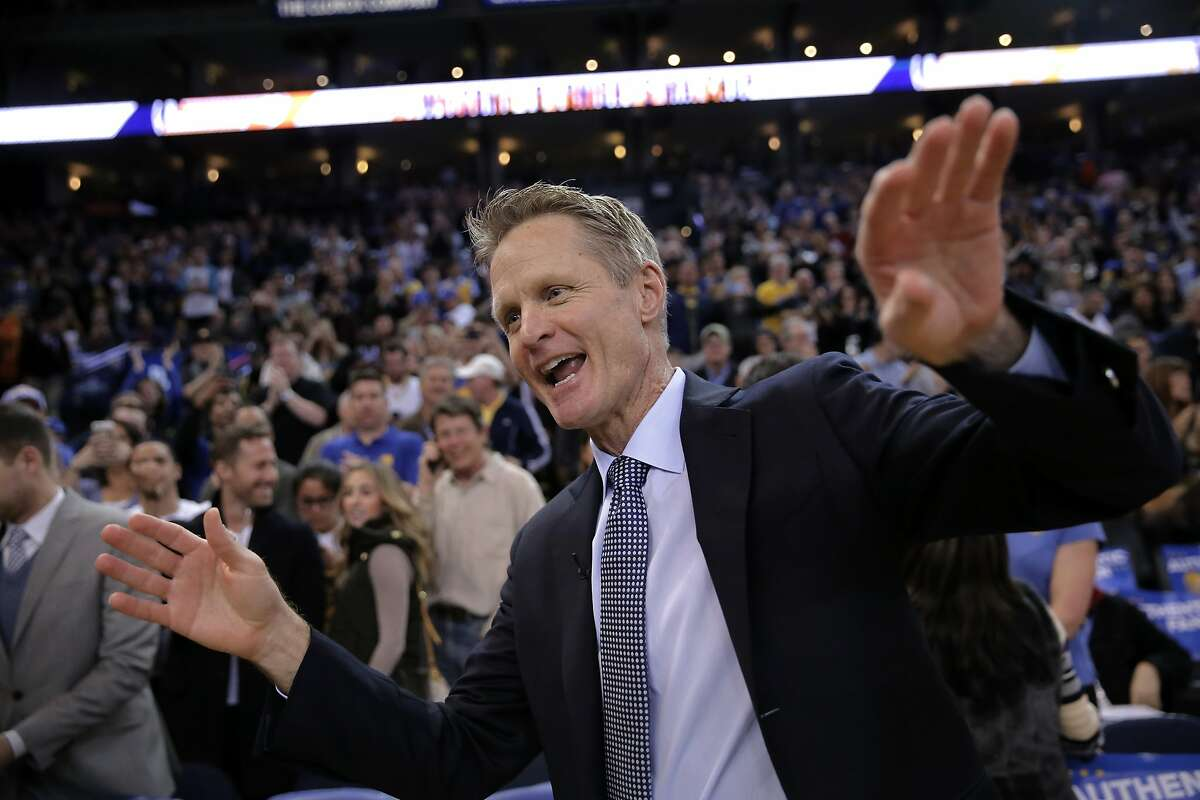 Warriors' head coach Steve Kerr tries to shoo away the attention he is getting as the Golden State Warriors take on the Indiana Pacers in NBA action during the first half at Oracle Arena on Fri. January 22, 2016, in Oakland, Calif.