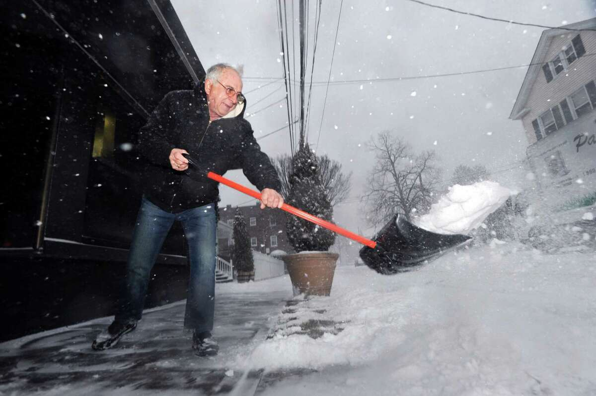 John Karipides, owner of the Famous Greek Kitchen on North Water Street, Byram, shovels snow from in front of his restaurant during the winter storm that hit Greenwich, Conn., Saturday morning, Jan. 23, 2016. Karipides said his business has been at 10 North Water Street for nearly 40 years and he also said he never closes the restaurant because of snow.