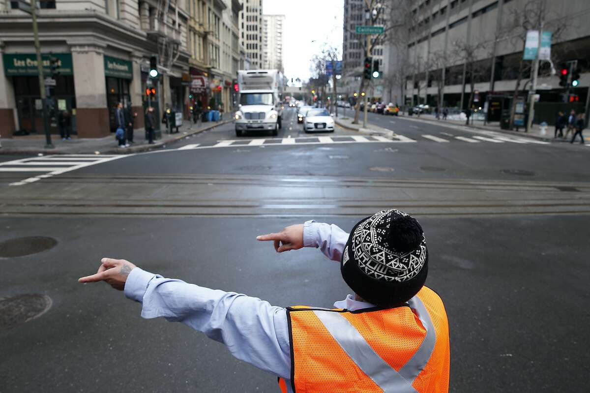 Andrew Thebpanya redirects traffic onto California Street from southbound Drumm Street at the site of Super Bowl City in San Francisco, Calif. on Saturday, Jan. 23, 2016. Traffic is sure to be a nightmare while street closures are in effect in the area near the Embarcadero and Market Street west to Beale Street.