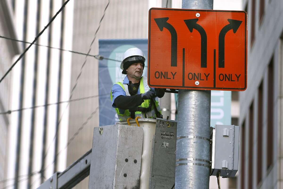 An MTA sign crew hangs temporary detour signs on Main Street to steer traffic away from the Super Bowl City fan zone in San Francisco, Calif. on Saturday, Jan. 23, 2016. Traffic is sure to be a nightmare while street closures are in effect in the area near the Embarcadero and Market Street west to Beale Street.